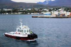 14 en zie dan hoe twee kleine slepers ons naar dieper water van de Eyjafjörður (de Eilandfjord) loodsen.