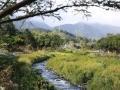 aan een smalle, woest stromende rivier met aan één kant uitzicht op de bergen