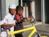 en een jochie dat zijn vriendje leert fietsen.