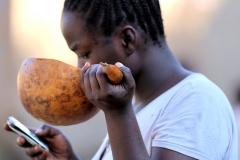 Dit 'moderne' meisje drinkt nog wel uit een kalebas, maar kijkt intussen op haar mobieltje!